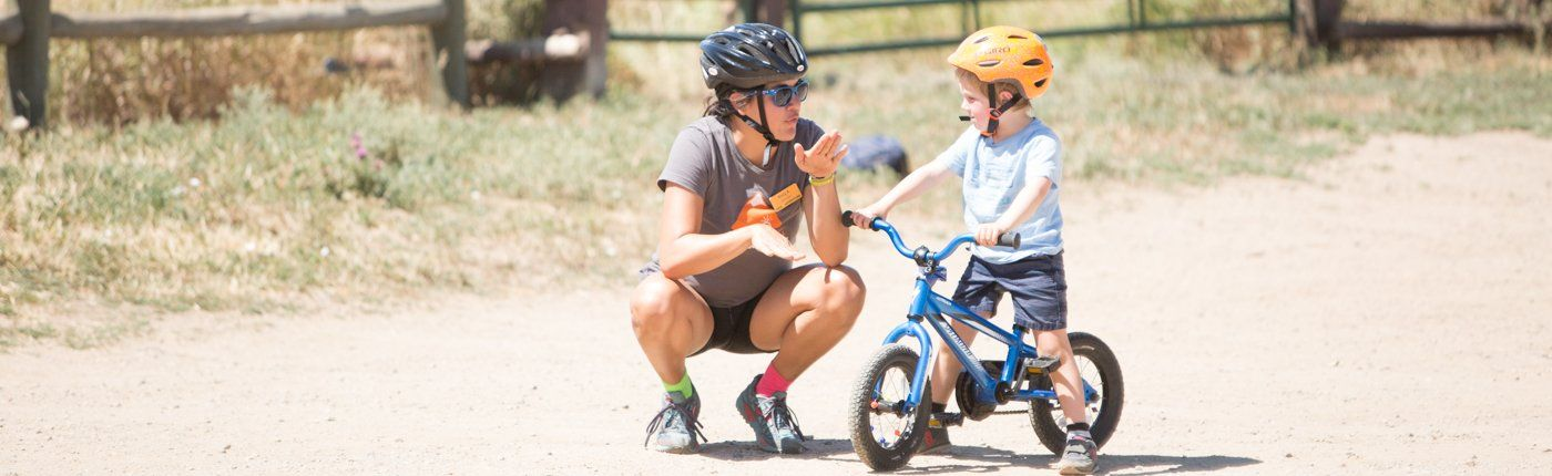 instructor teaching kid to bike at summer camp