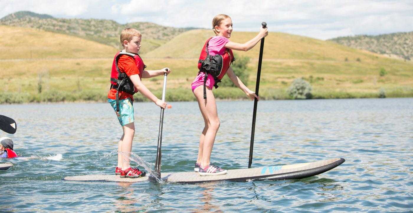 Kids standup paddle boarding at summer camp