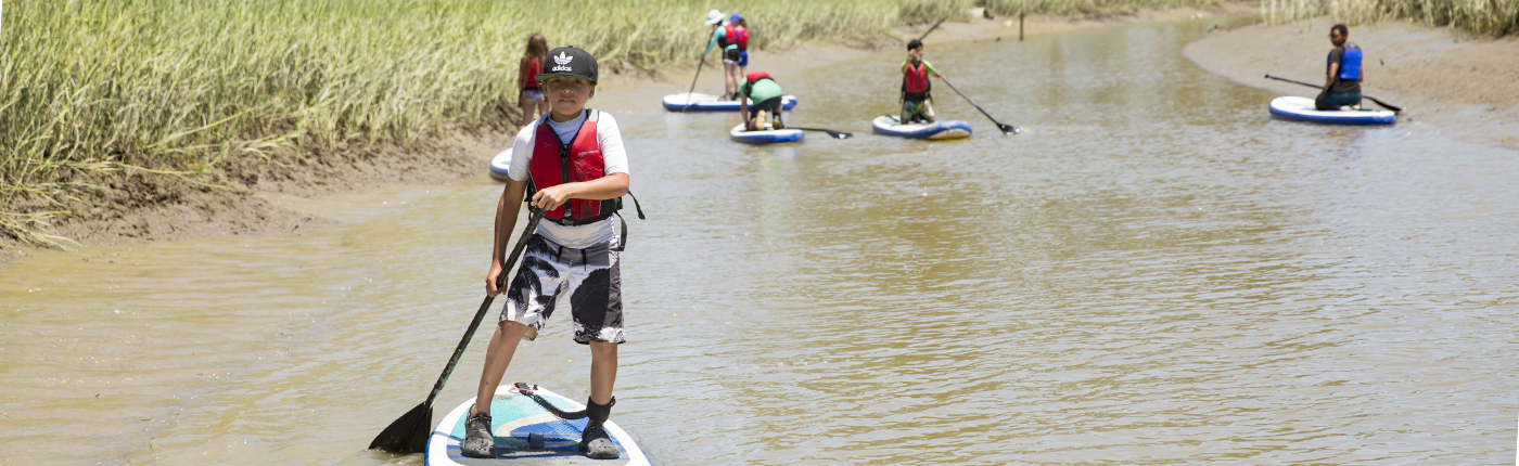 kids stand up paddle boarding at camp