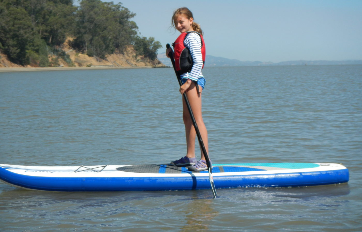 kids stand up paddle boarding at summer camp